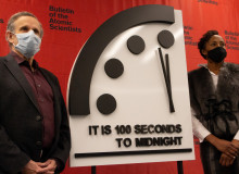 """Robert Rosner and Suzet McKinney stand on either side of the Doomsday Clock, which reads """"It is 100 seconds to midnight."""""""